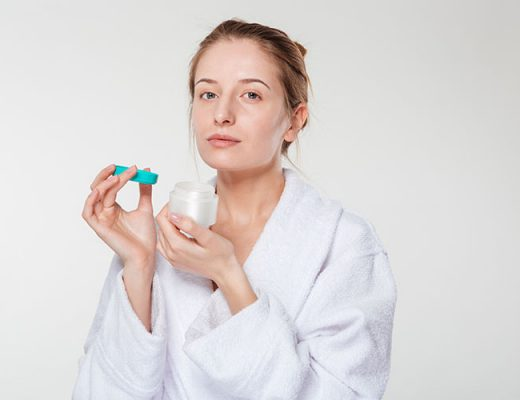 Beautiful woman holding cream