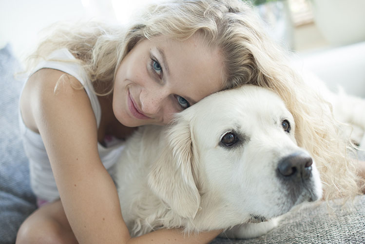 Beautiful woman hugging dog on sofa