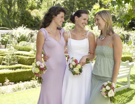 Bride with two women in garden holding bouquets
