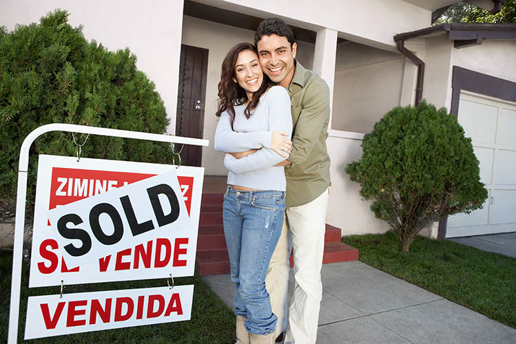 Couple standing in front of house with sold sign