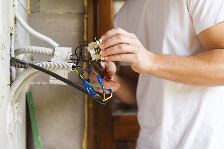 electrician repairing a wall plug
