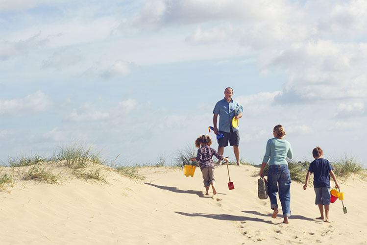 family walking up sand dune on beach