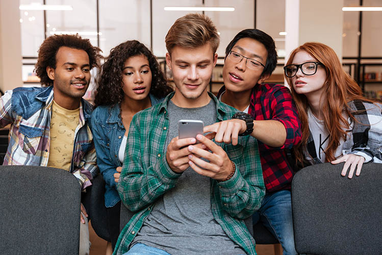 friends sitting and using mobile phone together