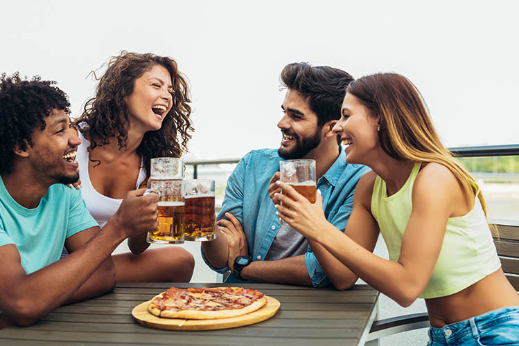 group of happy friends with beer and pizza