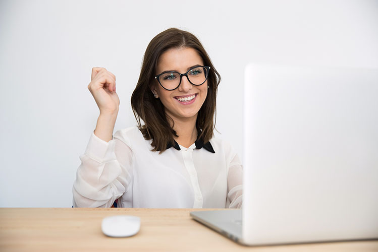 Happy businesswoman sitting at the table with laptop