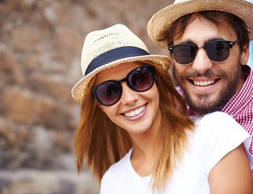 happy couple wearing hats and sunglasses