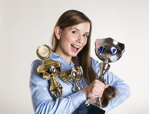 happy woman with 3 trophies in her hands