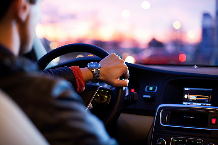 man driving a car in the evening