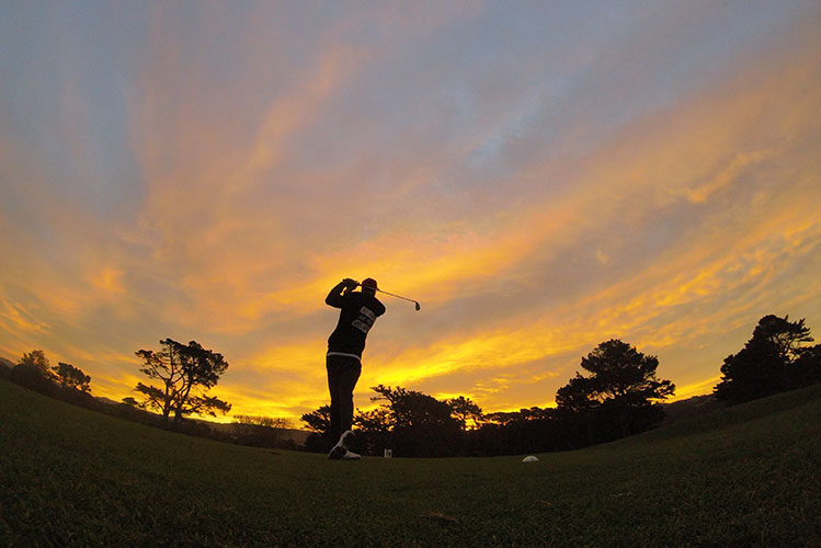 man playing golf sunset