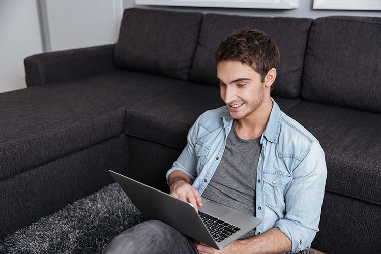 man sitting on carpet with laptop computer at home