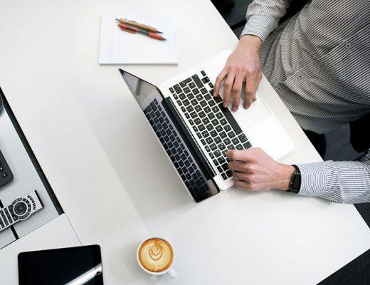 man working on mac laptop