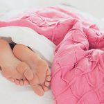 person sleeping under pink blanket