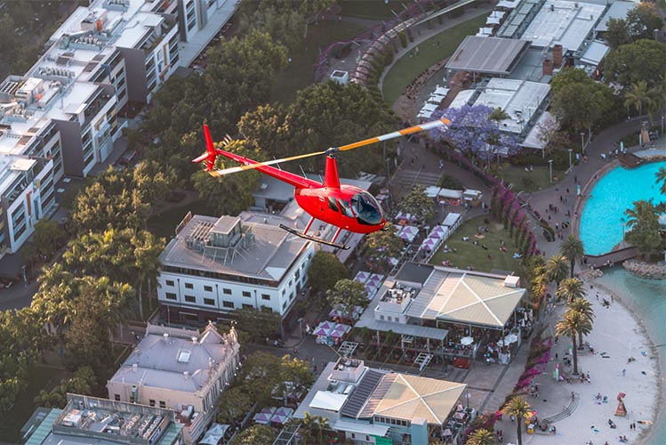 red helicopter flying over brisbane