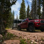 red toyota pickup and small travel trailer