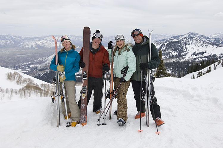 skiers holding skis on mountain
