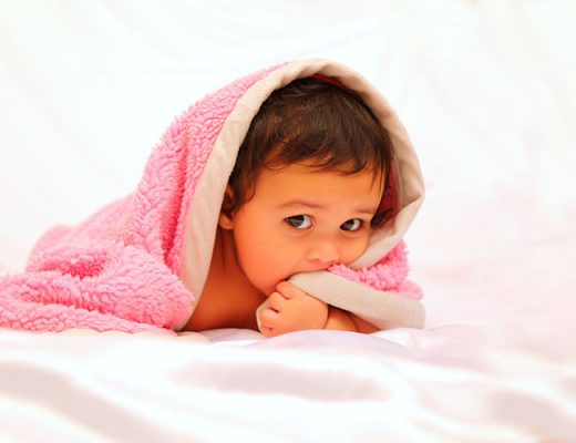 small baby under pink blanket