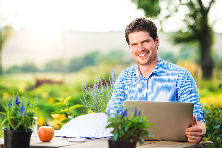 smiling man with laptop in the garden