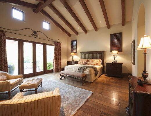 spacious high beamed bedroom with rug