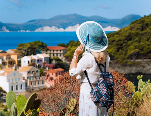 Tourist woman with blue sunhat, white clothes and travel backpack