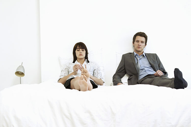 upset couple sitting on bed