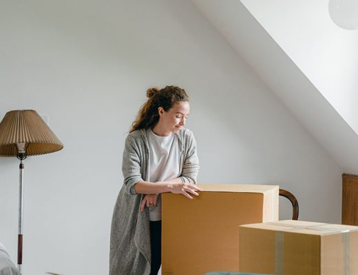 woman and cardboard boxes in the attic