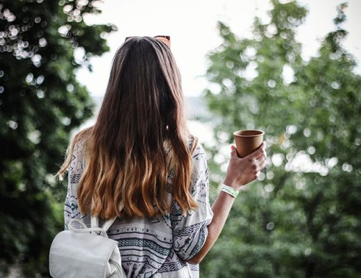 woman holding brown paper coffee cup