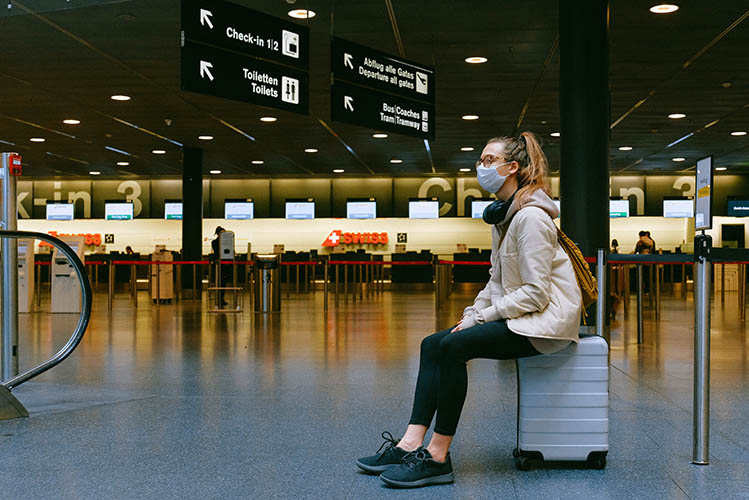woman sitting on luggage in the airport