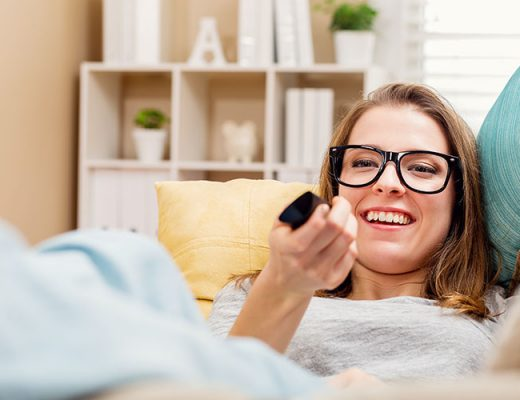 Happy young woman watching TV in the living room