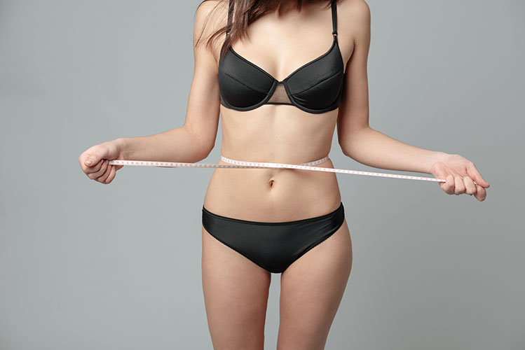 Woman with measuring tape weight loss