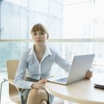 beautiful businesswoman with laptop sitting at table in office