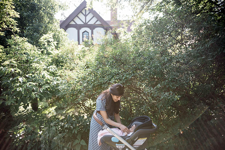 young mother caring for her baby in stroller