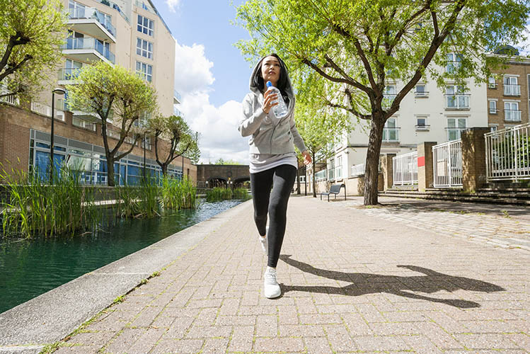 young woman jogging by canal