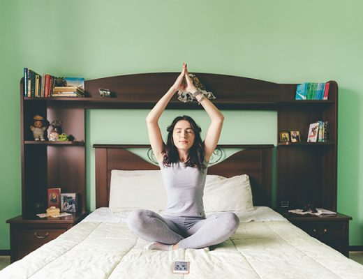 young woman meditating in her bedroom