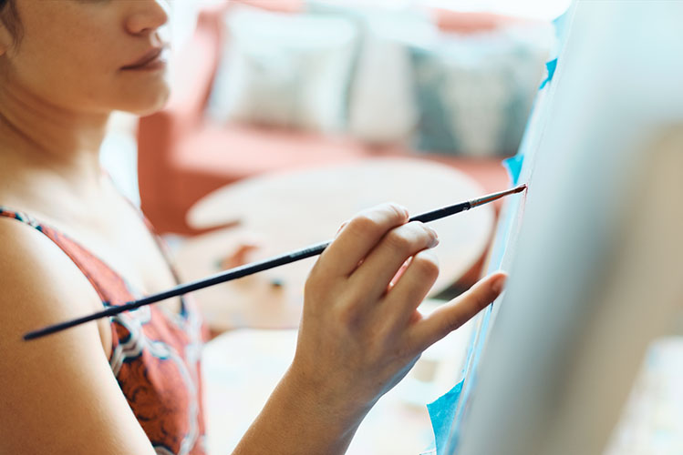 young woman painting in her home studio