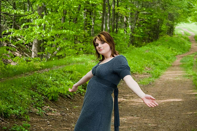 young woman posing on a wooded path